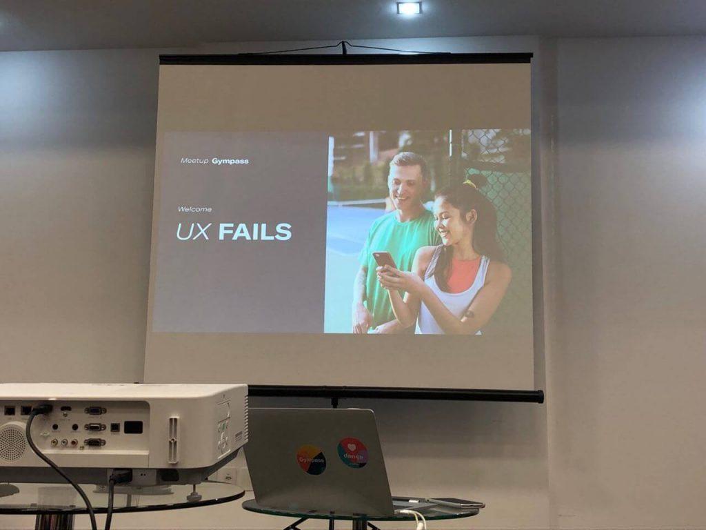 slide com os dizeres meetuy gimpass ux fails. na lateral uma foto de duas pessoas que aparentam serem gym rats