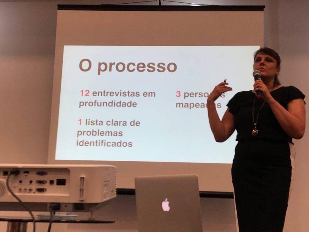 slide falando sobre o processo de um job da zoly, 12 entrevistas, 3 personas, 1 lista de problemas. Palestrante do lado direito com microfone na mão