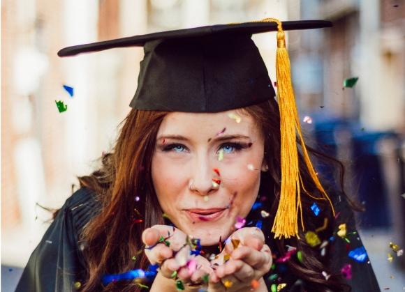 moça de olhos azuis e cabelos avermelhados com as maos juntas em frente ao rosto soprando algo, ela está vestida como uma formanda