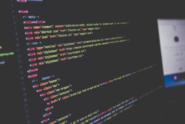editor de texto estilo sublime text mostrando o começo de um codigo HTML, bem ao fundo da foto se ve um browser com algo aberto