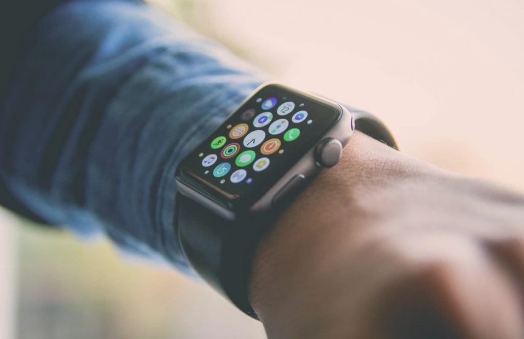 pulso de um homem com manga comprida, cor da pele meio morena, em destaque o apple watch comv arios icones na tela, pulseira preta